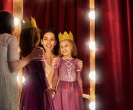 Cute little actress. Young mother and her daughter child girl in Princess costume on the background of theatrical scenes and mirrors Royalty Free Stock Photo