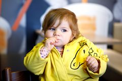 Cute little adorable baby girl sitting in indoor cafe. Happy toddler child eating bread. Colorful baby fashion clothes, blond hair girlie stock image