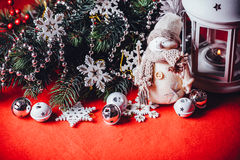 Cute little adorable snowman is standing near the white fairy lantern and decorated fir tree branch behind it. Stock Image