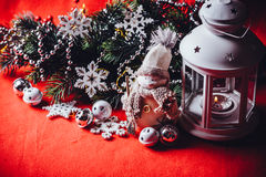 Cute little adorable snowman is standing near the white fairy lantern and decorated fir tree branch behind it. Royalty Free Stock Image