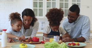 Little african boy and girl helping parents cutting vegetable salad