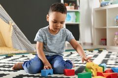 Cute little African-American child playing with building blocks on floor in kindergarten. Indoor activity royalty free stock photo