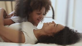 Cute little african child daughter tickling happy mother on bed