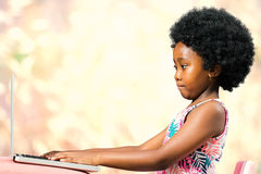 Cute little african girl with afro hairstyle typing on laptop. stock image