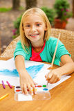 Cute little artist. Cute little girl drawing something on paper and smiling while sitting at the table and outdoors Royalty Free Stock Images