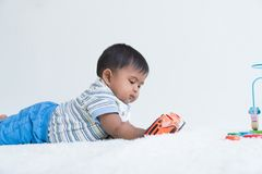 Cute little asian baby lying on soft blanket and play toy car royalty free stock images