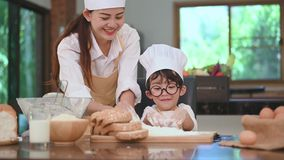 Cute little Asian boy and beautiful mother sifting dough flour in home kitchen on table for prepare to baking bakery and cake. Tha