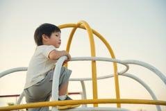 Cute little boy enjoys playing in a children playground. Cute little asian boy enjoys playing in a children playground Royalty Free Stock Images