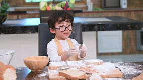 Cute little Asian boy with eyeglasses and apron playing and baking bakery in home kitchen as chef funny. Homemade food and bread. Education and learning stock video footage