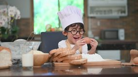 Cute little Asian boy with eyeglasses, chef hat and apron exciting with eggs for  first time experience to baking bakery in home k. Itchen funny. Homemade food stock video