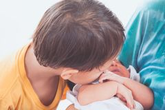 Cute little asian child boy kissing his newborn baby sister royalty free stock image