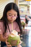 Cute girl drinking coconut water Stock Images