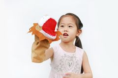 Cute Little Asian child girl hand wearing and playing Lion puppets on white background, Lion head.  royalty free stock photography