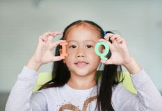 Cute little Asian child girl holding alphabet IQ Intelligence Quotient text on her face. Education concept royalty free stock photography