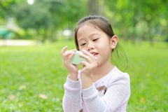 Cute little Asian child girl showing some food in her hands at green grass garden.  royalty free stock images