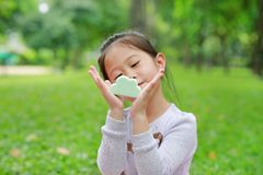 Cute little Asian child girl showing some food in her hands at green grass garden.  royalty free stock photo