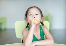 Cute little Asian child girl sing a song by plastic microphone at the kid room.  royalty free stock photo