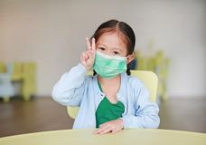 Cute little Asian child girl wearing a protective mask with showing two fingers for fight sitting on kid chair in children room.  royalty free stock image