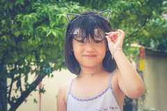 Cute little Asian Chinese girl and her glasses perched on top of her head. Autumn filter effect Stock Images