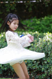 A cute little asian girl. Is spinning in joy Royalty Free Stock Photography