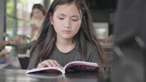 Cute little asian girl in casual clothes sitting enjoy reading book at cafe. Cute little asian girl in casual clothes is sitting enjoy reading book at cafe stock footage