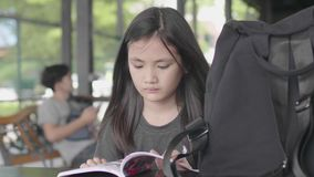 Cute little asian girl in casual clothes sitting enjoy reading book at cafe. Cute little asian girl in casual clothes is sitting enjoy reading book at cafe stock video footage