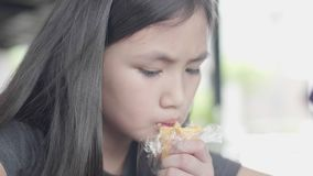 Cute little asian girl in casual clothes sitting enjoy reading book at cafe. Cute little asian girl in casual clothes sitting enjoy reading book and eating a stock video footage