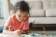Cute little asian girl drawing homework and writing with color Wax crayons on paper at home.  royalty free stock photo