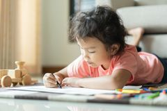 Cute little asian girl drawing homework and writing with color Wax crayons on paper in her home.  royalty free stock photography