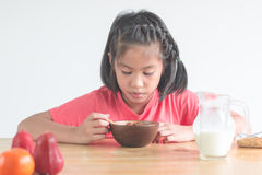 Cute little Asian girl eating cereal with the milk in the kitche Royalty Free Stock Image