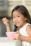 Cute little asian girl eating cereals in morning. Stock Photos