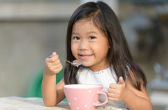 Cute little asian girl eating cereals in morning. Royalty Free Stock Photo