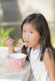 Cute little asian girl eating cereals in morning. Stock Images