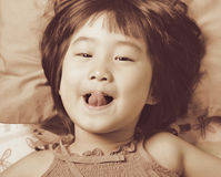 Cute little asian girl face while  playing in the bed Royalty Free Stock Images