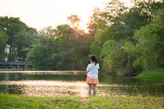 Cute little asian girl looking at the beautiful lake Royalty Free Stock Images