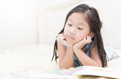 Cute little asian girl in nightdress reading a book. Stock Photo