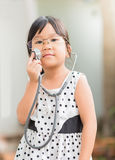 Cute little asian girl play in doctor costume. Royalty Free Stock Images