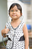 Cute little asian girl play in doctor costume. Stock Image