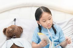 Cute little asian girl reading fairy tales book on bed Royalty Free Stock Photography