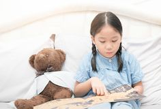 Cute little asian girl reading fairy tales book on bed Royalty Free Stock Images