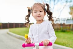 Cute Little Asian Girl Riding Scooter stock image