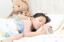 Cute little asian girl sleep and touch alarm clock on bed in the Stock Photography