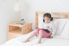 A cute little Asian girl, a Thai people wearing a white long-sleeved shirt, is sitting on bed and playing a tablet in bedroom. After she just woke up in the royalty free stock photos