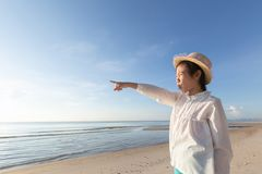 Cute little asian girl wear straw hat walking on the beach with. Looking out to the sea,concept summer vacation holiday stock photo