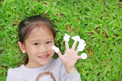 Cute little Asian kid girl lying on green grass lawn with showing empty white stickers on her fingers stock photo