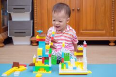 Cute little Asian 18 months / 1 year old toddler boy child having fun playing with colorful building blocks indoor in w-sitting po