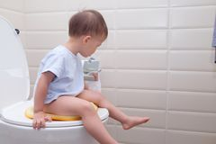 Cute little Asian 2 year old toddler baby boy child sitting on the toilet modern style with a kid bathroom accessory. And holding & playing with toilet paper royalty free stock image
