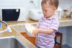 Asian 2 year old toddler baby boy child standing and having fun doing the dishes / washing dishes in kitchen stock photos