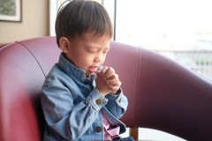 Little Asian 3 - 4 years old toddler boy child praying with eyes closed, hands clasped together for prayer at home,  World Day of