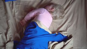 A cute little awakened toddler spins around in a blue blanket, then turns on its side and freezes. Little baby girl stock video footage